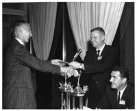 Dick Swanson receives an award at a ceremony. Joe Hill is the presenter.