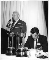 Paul Barrett and Dave Diles at an awards ceremony. Barrett is speaking at the microphone.