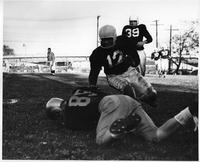 An action play from the 1960 football team. It looks as if #85 is recovering a fumble