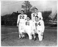 Four football players, #s 22, 61, 67, and 84 pose for a portrait. The bleachers are visible in the background