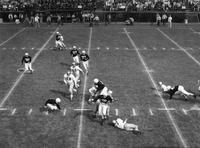 An action shot of a football play being run--#46 has the ball.