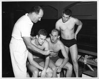 Coach John Hussay, Bill Durgis, Frank Michalik, Jim Craft. Three swimmers look at their times as the coach dons a stopwatch.