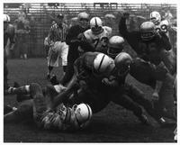 A line plunge, a gang tackle and a pile-up--three football terms becoming reality in this excellent shot taken during the Wayne State-John Carroll football game of October 13, 1962 at Tartar Field in Detroit. John Carroll won, 67-14.