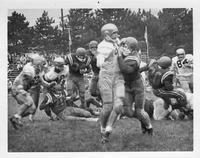 An action play from 1962 football with two American flags framing the background.