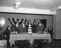Mrs. Lovejoy cuts a cake at a League of Women Voters' banquet. Mrs. Sargent is also present.