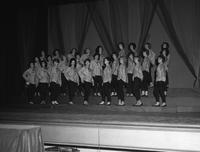 The PanHellenic Singers perform a number in matching outfits.