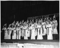 The PanHellenic Singers perform a number in matching gowns and pointed hats.