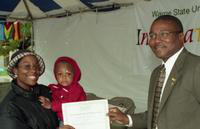 A woman with a baby receives a certificate from President Irvin Reid at the International Fair.