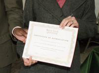 An woman receives a certificate from President Irvin Reid at the International Fair.