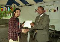 A man receives a certificate from President Irvin Reid at the International Fair.