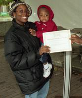 An woman with a baby receives a certificate from President Irvin Reid at the International Fair.