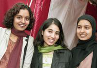 Three women pose for a photo at the International Fair.