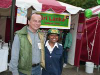 A man and a woman in front of the Sri Lankan booth pose for a photo at the International Fair.