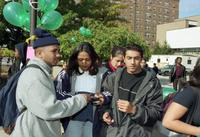 Students wait in a line at the International Fair. Chatsworth Apartments is visible in the background.