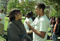 Two students talk at the International Fair with the Undergraduate Library and Biological Sciences Buildings in the background.