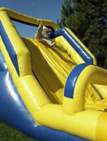 A student at the International Fair jumps down a slide bounce house.