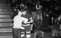 A player hands a corsage to his mother as they embrace in front of the crowd.