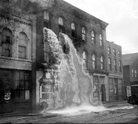 Prohibition; Raids. Detroit. destroying confiscated booze. 2 pix- liquor overflowing from 2nd floor balcony (1 pix is copy). 1 pix - man with axe & large pile of liquor bottles 12-10-29. 1 pix - police at brewery - large vats