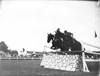 Pierce, Chas D. Jr. Jr. Horseman Standing beside horse with brother Jack Hurdling .