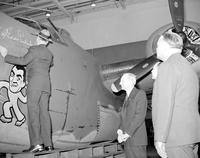 Rickenbacker, Captain Eddie (Aviator); Tour of Defense Plant. -Signing Name on Bomber. -At Willow Run Bomber Plant. -With; Henry  Ford