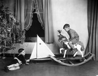 Christmas Scenes; Christmas Trees. Children playing beside Chirstmas Tree with rocking horse & sailboat.