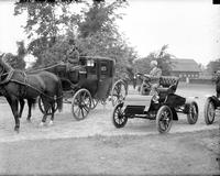 Ford Motor Company; Anniversary; 40th. -Henry Ford Driving Old Model Car Passing a Stage Coach