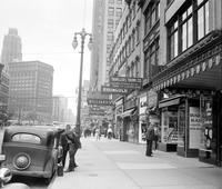 streets; Woodward; downtown. before widening. Woodward Avenue. showing signs over hanging the sidewalk