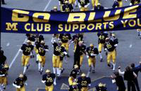 "Colleges. University of Michigan. Football. Team. players cheering under ""go blue"" sign. used Nov 20, 1980."