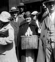 Prohibition; Canada; Repeal. scenes in Windsor where liquor ban was lifted June, 1927. - old woman in middle of crowd with picnic basket smiling .