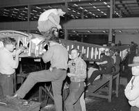 "Ford Motor Co. ; Plants; Willow Run. Production of Consolidated B-24 ""Liberators"". Moving huge tail section onto bomber on production line"