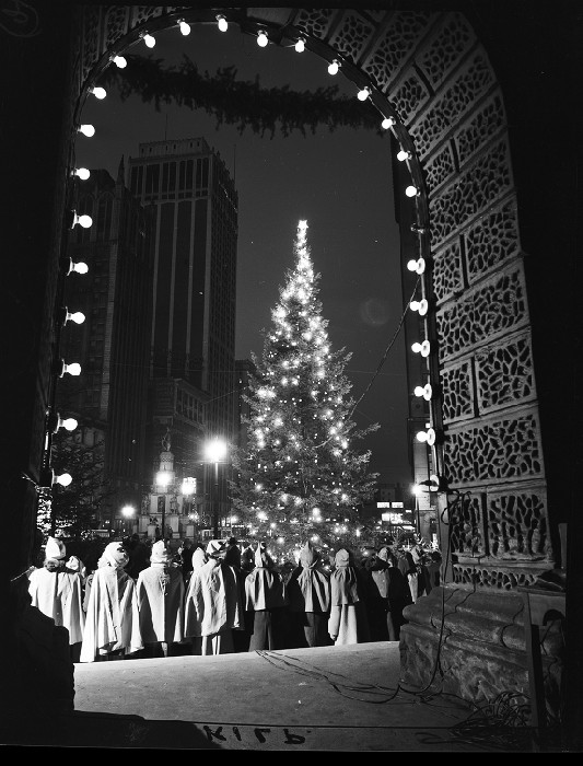 Carollers in front of Detroit's downtown Christmas tree